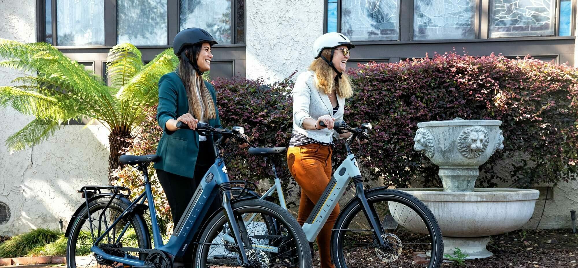 To kvinder med hjelm og cykel