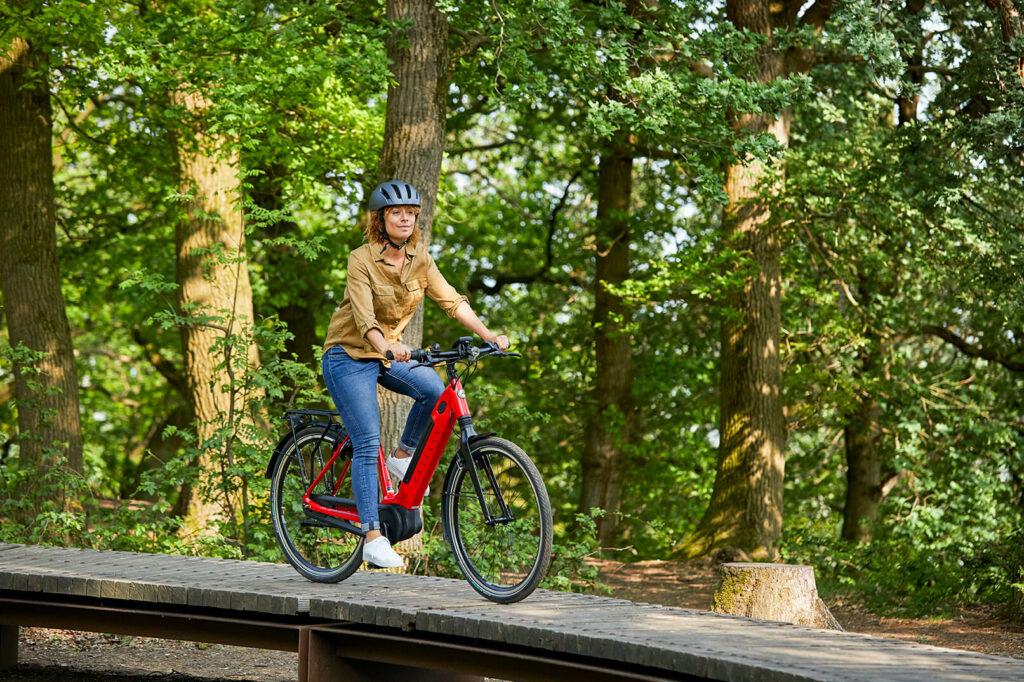 Kvinde på rød cykel i skoven