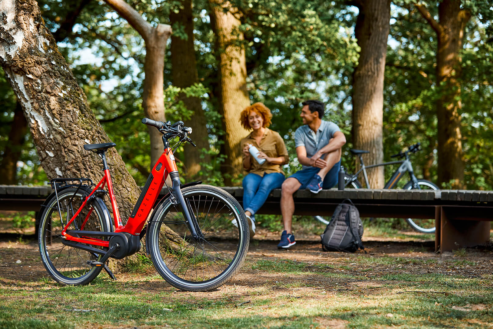 Mand og kvinde med rød cykel i forgrunden