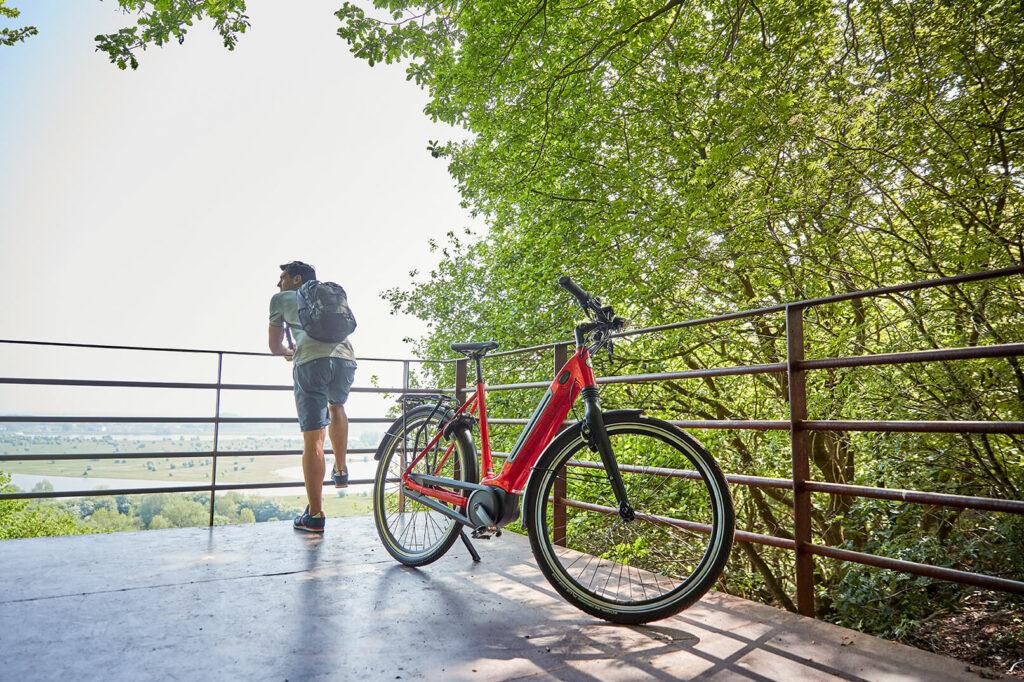 Mand med rød cykel ved udsigten