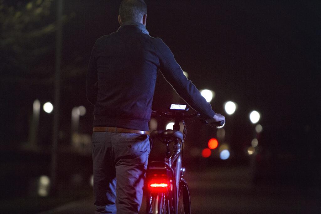 Mand går med cykel i mørket |  Cykellygter
