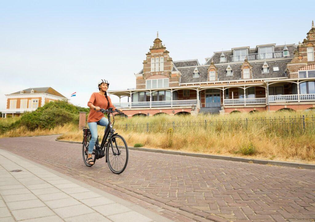 Kvinde med hjelm på cyklen