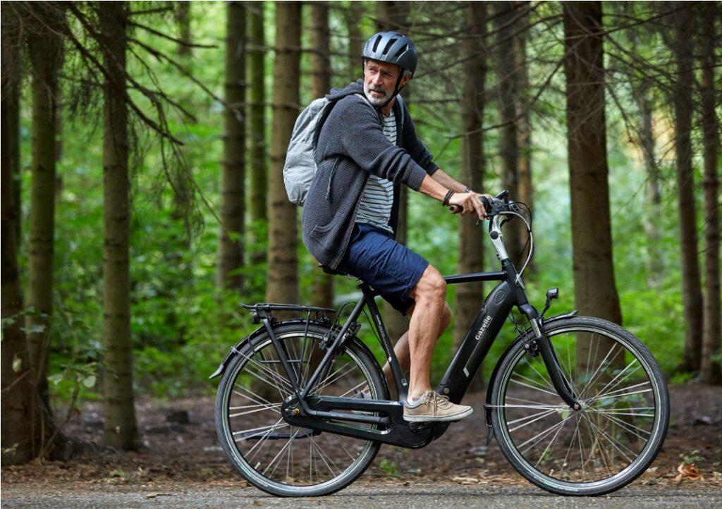 Mand med rygsæk på en cykel i skoven