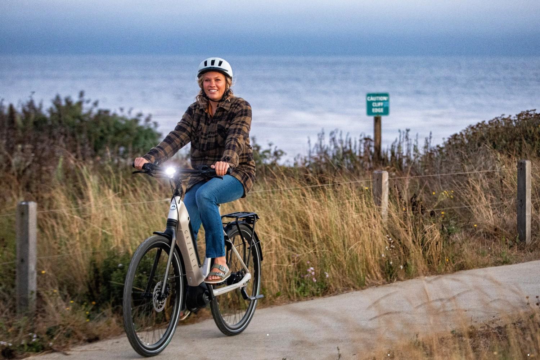Woman riding Dutch bike by the sea